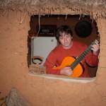 Flagrante do poeta Diovvani Mendonça, viola na mão, em sua casa caipira