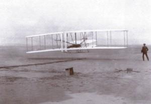 O Flyer dos irmãos Wrigth, que só se erguia do chão com a vergonhosa ajuda de uma catapulta, para logo mais, em voo artificial e mal controlado, perder altura e cair de volta ao solo.