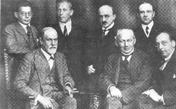 Em pé (esq. p/ dir.): Otto Rank, Karl Abraham, Max Eitingon e Ernest Jones.