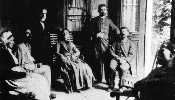 Liebaut (em pé, à esq.) em sua clínica, acompanhado de um assistente (em  pé) e alguns de seus pacientes